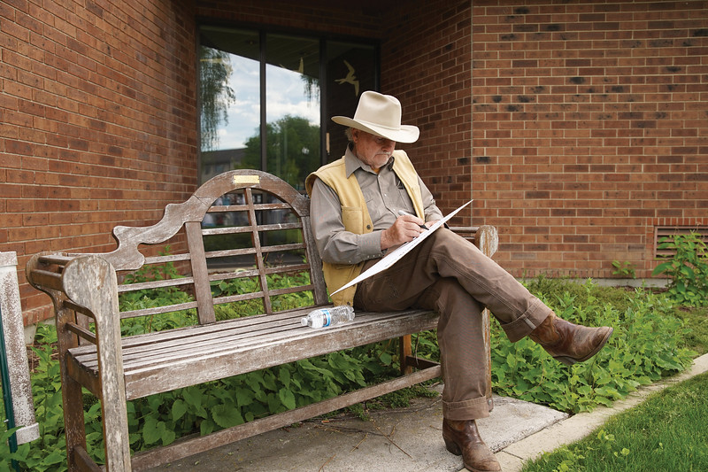 Matthew Gaston | The Sheridan Press<br>Rod Parr sits quietly on a bench outside the Sheridan Fulmer Public Library and makes a sign to show his support for at the Black Lives Matter Solidarity Protest Friday, June 5, 2020.