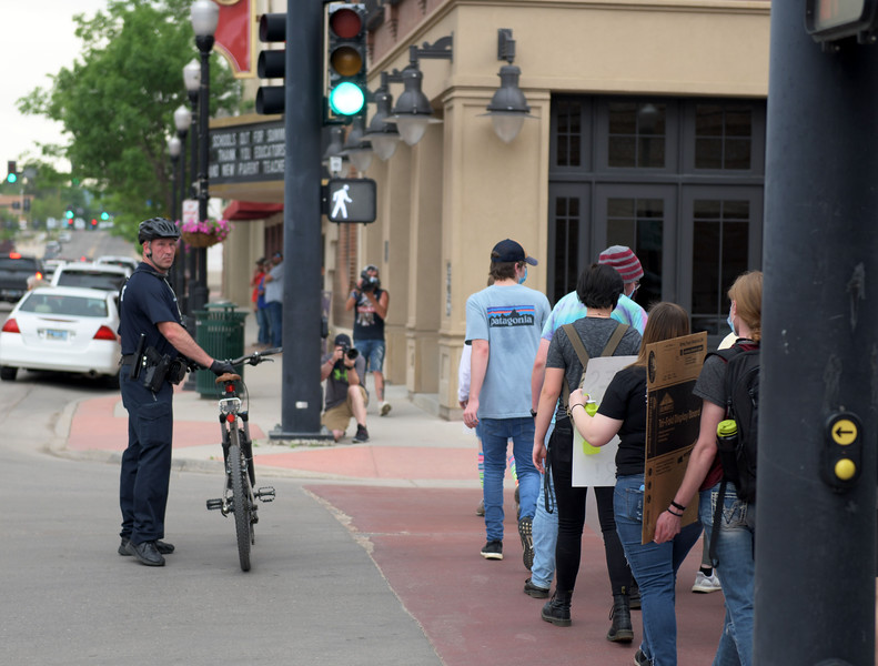 Allayana Darrow | The Sheridan Press<br /> Sheridan Police Department Sgt. Jerry Rasmussen guides protesters across an intersection Friday, June 5, 2020.