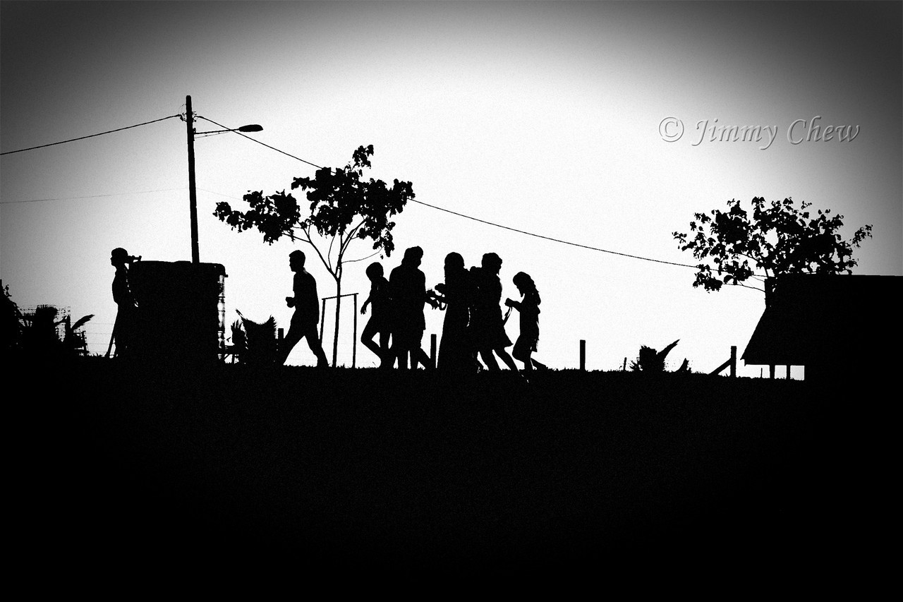 B&W silhouette of a group of people walking across the farmland. This photo is from my previous visit.
