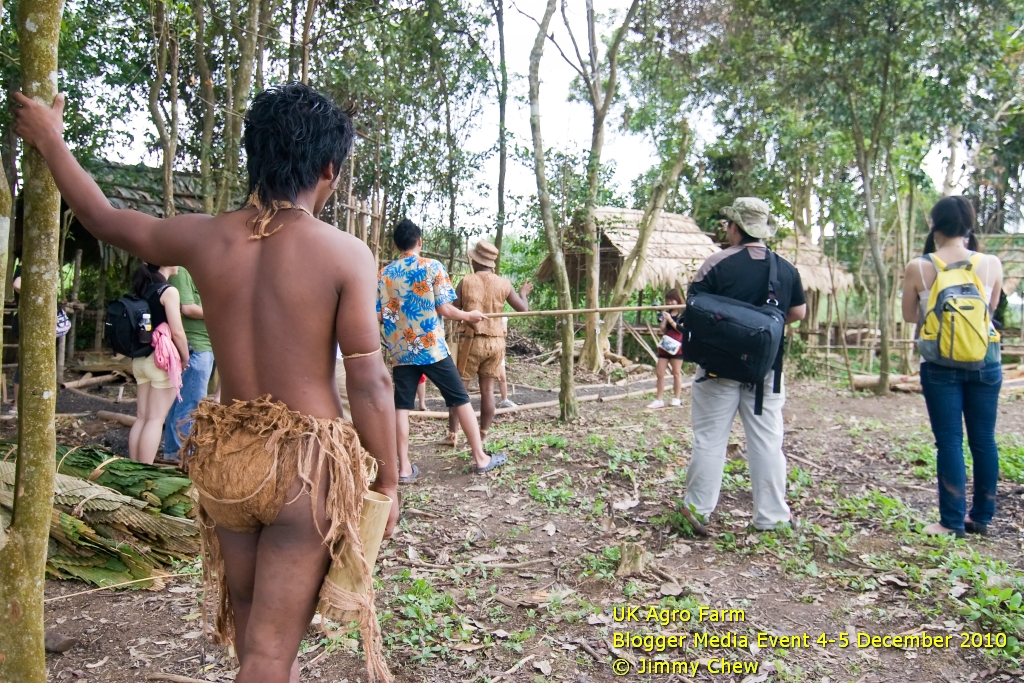 Another Orang Asli watching by as the group hears Oh Oh explaining the use of blowpipes.