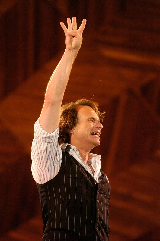 """Former Van Halen frontman David Lee Roth signals """"Four"""" with his hands after singing during a rehearsal for Boston's Fourth of July celebration at the Hatch Shell in Boston, Saturday, July 3, 2004."""
