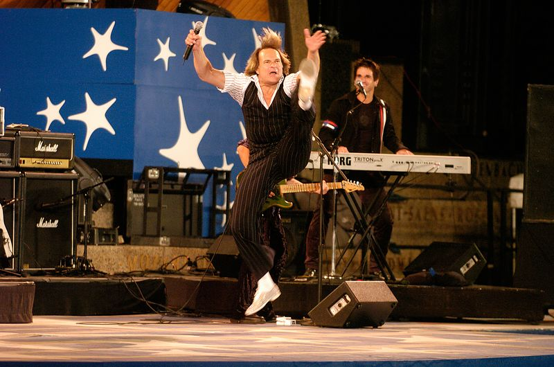 """Former Van Halen frontman David Lee Roth leaps during a rehearsal performance of """"Jump!"""" for Boston's Fourth of July celebration at the Hatch Shell in Boston, Saturday, July 3, 2004."""