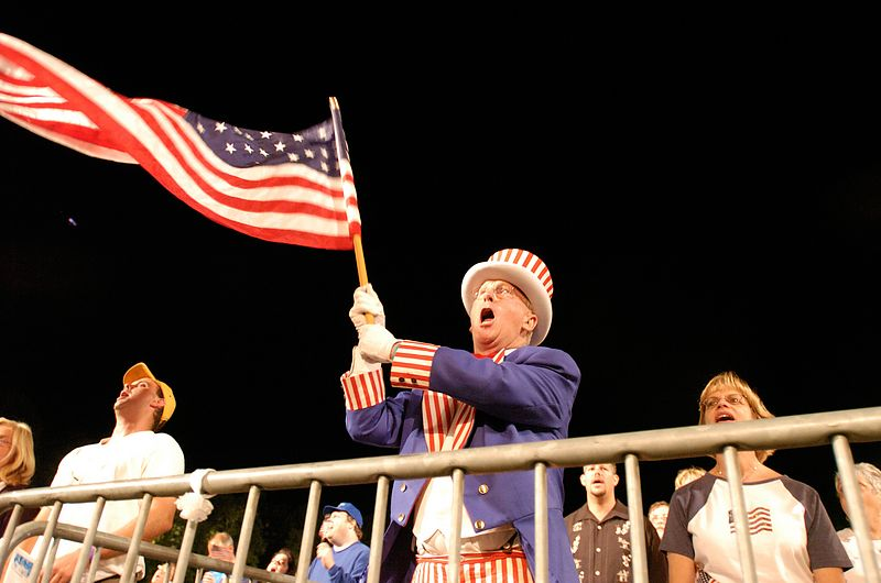 A man calling himself 'Uncle Sam Rounseville' of Quincy, Massachusetts sings along during a rendition of 'God Bless America', while waving a U.S. flag, in Boston, Saturday, July 3, 2004.