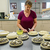 Dana Waller is in charge of baking the pies for the Bostwick Blueberry Festival. Here she puts the finishing touches on pies to be baked. With the 650 pounds of blueberries they got, they'll be making 278 pies (50 more than last year), 360 muffins, blueberry crumb cake and blueberry crunch cake, in addition to all the pancakes served at the breakfast. Fran Ruchalski/Palatka Daily News