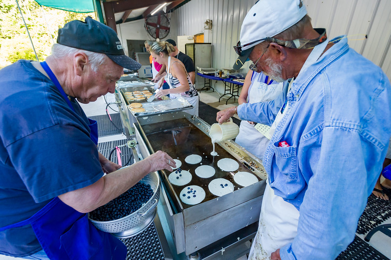 John LaForge, right, pours out pancake batter while Wayne McClain sprinkles blueberries on to each one for all of those folks waiting for blueberry pancakes at the Bostwick Blueberry Festival on Saturday. Fran Ruchalski/Palatka Daily News