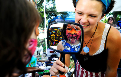 Mia Teicher, 4, imitates a cat by roaring as face painter Amber Jarvis holds up the mirror at the Boulder Creek Hometown Fair in Boulder Saturday, Sept. 5, 2009. Along with the weekly farmer's market, the fair hosted fair games, face painting, and live music. DAILY CAMERA/Kasia Broussalian For more photos and a video of the event, please visit www.dailycamera.com