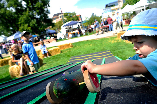 """Oliver Merkner, 3, of Denver, rolls down his decorated zucchini before the start of the Great Zucchini Race at the Boulder Creek Hometown Fair in Boulder Saturday, Sept. 5, 2009. Along with the weekly farmer's market, the fair hosted fair games, face painting, and live music.<br /> DAILY CAMERA/Kasia Broussalian<br /> For more photos and a video of the event, please visit  <a href=""""http://www.dailycamera.com"""">http://www.dailycamera.com</a>"""