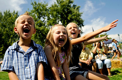 (From left to right) Landon Ungerman, 5,  of Aurora, and his two sisters Amaren, 4, and Kendall, 10, cheer on their zucchini they entered in the Great Zucchini Race at the Boulder Creek Hometown Fair in Boulder Saturday, Sept. 5, 2009. Along with the weekly farmer's market, the fair hosted fair games, face painting, and live music. DAILY CAMERA/Kasia Broussalian For more photos and a video of the event, please visit www.dailycamera.com