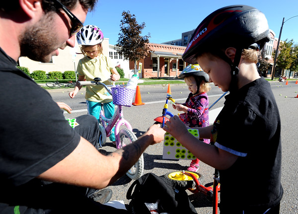 """Brennan Bushman, left, of Community Cycles, hands out stickers to Ellei Stanzel, 6, her sister, Addy, 2, and brother Owen, during the celebration on Pearl Street.<br /> Boulder Green Streets, a celebration of sustainability and public health, was held on Pearl Street  on Sunday.<br /> For more photos of Green Streets, go to  <a href=""""http://www.dailycamera.com"""">http://www.dailycamera.com</a>.<br /> Cliff Grassmick / September 19, 2010"""