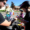 "Brennan Bushman, left, of Community Cycles, hands out stickers to Ellei Stanzel, 6, her sister, Addy, 2, and brother Owen, during the celebration on Pearl Street.<br /> Boulder Green Streets, a celebration of sustainability and public health, was held on Pearl Street  on Sunday.<br /> For more photos of Green Streets, go to  <a href=""http://www.dailycamera.com"">http://www.dailycamera.com</a>.<br /> Cliff Grassmick / September 19, 2010"
