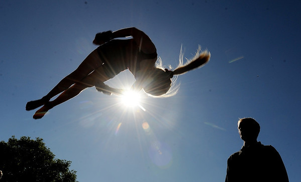 "Heather Betts, 12, does a flip from a mini trampoline, as her instructor, Doug Felkley, of the City of Boulder, looks on. The gymnastics demonstration was one of several active things to see on Pearl Street.<br /> Boulder Green Streets, a celebration of sustainability and public health, was held on Pearl Street  on Sunday.<br /> For more photos of Green Streets, go to  <a href=""http://www.dailycamera.com"">http://www.dailycamera.com</a>.<br /> Cliff Grassmick / September 19, 2010"