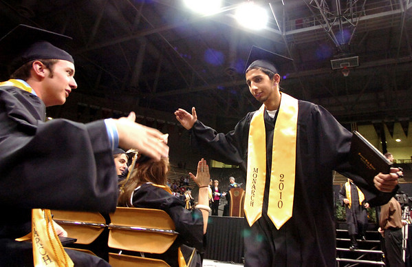 "Chris Carlton, left, reaches out to congratulate Cameraon Sadafi after Sadafi left the stage during the Monarch High School Commencement at the Coors Events Center on the CU Boulder Campus on Saturday May 22, 2010.<br /> For more photos and a video of the graduation go to  <a href=""http://www.dailycamera.com"">http://www.dailycamera.com</a><br /> Photo by Paul Aiken / The Camara /"