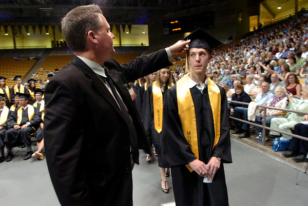 "Ken Henderson, of Grad Images sets up the tasel of Daniel Eng before he has his photo taken during the Monarch High School Commencement at the Coors Events Center on the CU Boulder Campus on Saturday May 22, 2010.<br /> For more photos and a video of the graduation go to  <a href=""http://www.dailycamera.com"">http://www.dailycamera.com</a><br /> Photo by Paul Aiken / The Camara /"