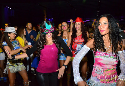 Women in mask dances with Brazilian Carnaval performers