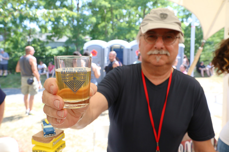 Wayne Little serves up some Watchustt Summer Brew in one of the glasses you got at the annual Nashua River Brewers Festival on Saturday at Riverfront Park in Fitchburg. SENTINEIL & ENTERPRISE/JOHN LOVE