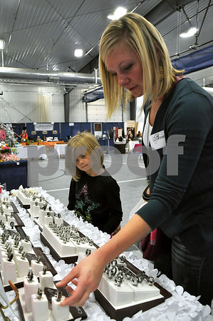 -Messenger photo by Joe Sutter<br /> <br /> Brittany Gallentine, of Coalville, looks over some men's carbon fiber wedding bands at the Gilbert Jewelers booth, watched by 7-year-old Abbi Tucker. Gallentine's wedding is set for Sept. 2014.