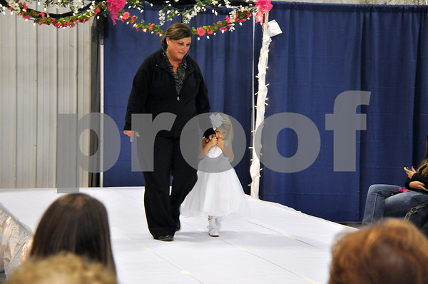 -Messenger photo by Joe Sutter<br /> <br /> Rylee O'Brion, 3, gets a little help from her grandma Barb O'Brion to overcome her stage fright for the fashion show at the annual Bridal Spectacular.