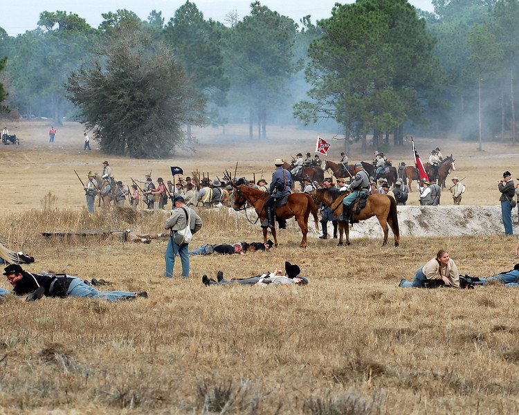 Confederate forces stand among the dead and dying during a lull in the battle.