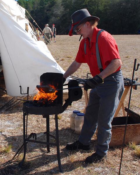 A blacksmith stokes his fire.