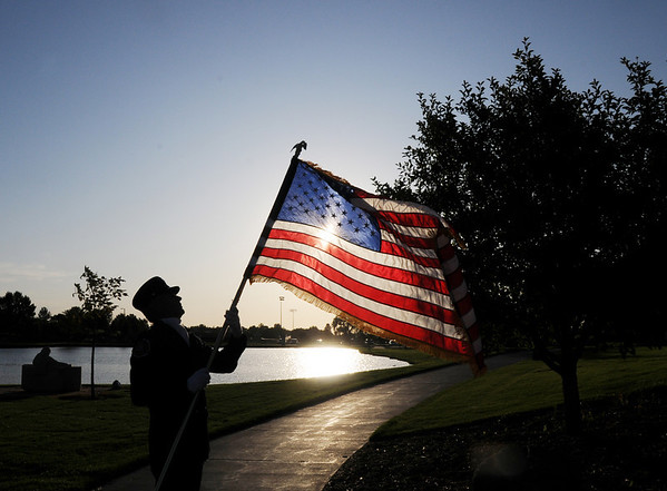 Lt. Don Wiercinski, North Metro Fire Rescue, unfolds the US flag before the ceremony on Friday at the 9/11 Memorial in Community Park in Broomfield.<br /> <br /> Sept. 11, 2009<br /> Staff photo/David R. Jennings