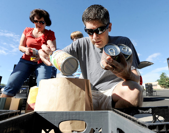 "Jeff Kerrand separates donated food items during the food drive on Saturday. Doris Jones works in the background.<br /> As part of Colorado Cares Day, local  Broomfield churches and City Council members  participated in a food drive for Broomfield FISH.<br /> For more photos an a video, go to  <a href=""http://www.broomfieldenterprise.com"">http://www.broomfieldenterprise.com</a>.<br /> Cliff Grassmick  / July 28, 2012"