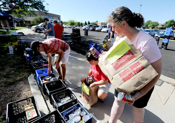 "Michelle Pearson, right, joins other volunteers sorting donated food items on Saturday.<br /> As part of Colorado Cares Day, local  Broomfield churches and City Council members participated in a food drive for Broomfield FISH.<br /> For more photos an a video, go to  <a href=""http://www.broomfieldenterprise.com"">http://www.broomfieldenterprise.com</a>.<br /> Cliff Grassmick  / July 28, 2012"