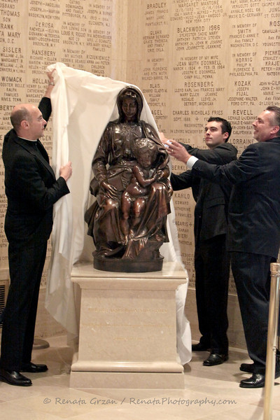 L-R: Msgr. Walter Rossi, Daniel Gaddy, Lonnie Gaddy unveil new Bruges Madonna by Michelangelo, a bronze replica, at the National Shrine - Crypt level.