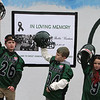"""Current and former participants in Billerica youth sports assemble at Lampson Field to honor the late Daniel """"Bubba"""" Goodwin as his funeral procession passes. From left, Jake Giordano, 10, of Billerica, Dayton Jackson, 9, of Hanscom AFB, and Hailey Bornstein, 8, of Billerica. (SUN Julia Malakie)"""