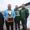 """Current and former participants in Billerica youth sports assemble at Lampson Field to honor the late Daniel """"Bubba"""" Goodwin as his funeral procession passes. From left, Kevin McCormick of Wellington, Florida, Billy Burrows of Loxahatchee, Florida, Todd Micciche and Mike Pellegrino of Billerica, with the 1991 Eastern Mass championship trophy of the Pop Warner team they were on, coached by Bubba Goodwin. (SUN Julia Malakie)"""