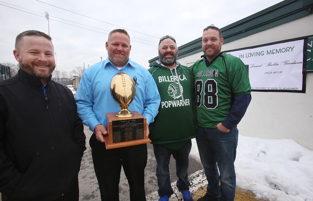 """. Current and former participants in Billerica youth sports assemble at Lampson Field to honor the late Daniel \""""Bubba\"""" Goodwin as his funeral procession passes. From left, Kevin McCormick of Wellington, Florida, Billy Burrows of Loxahatchee, Florida, Todd Micciche and Mike Pellegrino of Billerica, with the 1991 Eastern Mass championship trophy of the Pop Warner team they were on, coached by Bubba Goodwin. (SUN Julia Malakie)"""