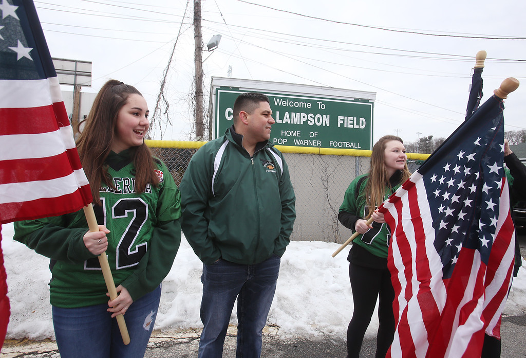 """. Current and former participants in Billerica youth sports assemble at Lampson Field to honor the late Daniel \""""Bubba\"""" Goodwin as his funeral procession passes. Waiting for procession to arrive, from left: Olivia Venezia, 14, her father Dan Venezia, and Sarah Green, 14, all of Billerica. (SUN Julia Malakie)"""