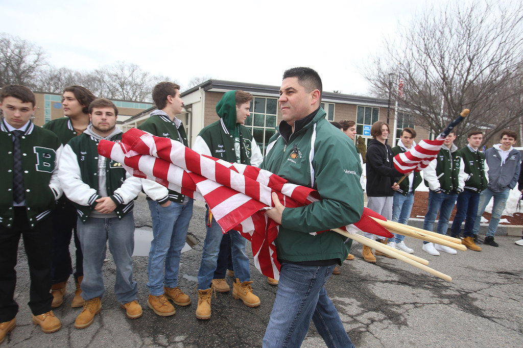 """. Current and former participants in Billerica youth sports assemble at Lampson Field to honor the late Daniel \""""Bubba\"""" Goodwin as his funeral procession passes. Dan Venezia of Billerica passes out flags before the procession. (SUN Julia Malakie)"""