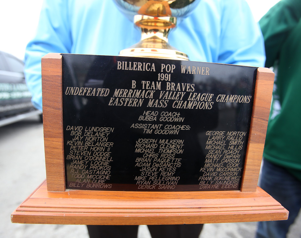 """. Current and former participants in Billerica youth sports assemble at Lampson Field to honor the late Daniel \""""Bubba\"""" Goodwin as his funeral procession passes. Billy Burrows of Loxahatchee, Florida, holds the championship trophy of the Pop Warner team he was on, coached by Bubba Goodwin. (SUN Julia Malakie)"""