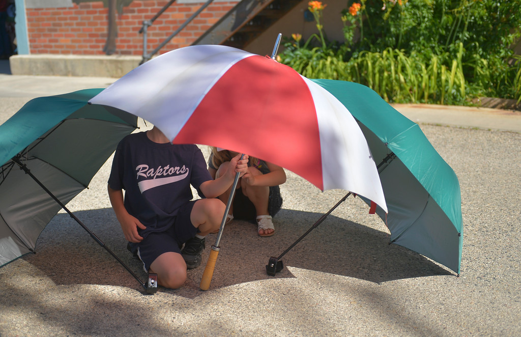 Justin Sheely | The Sheridan Press <br /> Eight-year-old Paxton Cotant, left, and sister Kaelyn Cotant of Buffalo play under umbrellas prior to the parade during the sixth annual Longmire Days Saturday on Main Street in Buffalo, Wyoming. The show is based on local author Craig Johnson's novels set in the fictional town of Durant, inspired by the town of Buffalo. Longmire's sixth and final season will be on Netflix sometime this year.
