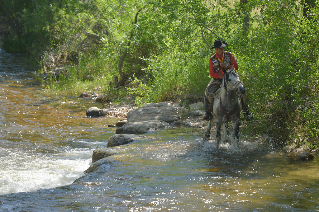 Justin Sheely | The Sheridan Press <br /> A parade member leads his horse to water in the Clear Creek during the sixth annual Longmire Days Saturday in Buffalo, Wyoming. The show is based on local author Craig Johnson's novels set in the fictional town of Durant, inspired by the town of Buffalo. Longmire's sixth and final season will be on Netflix sometime this year.