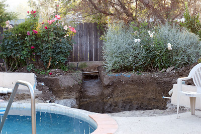 The bare hole - it took the workers about 3 days to cut the wall & concrete and dig it out.  We lost about 6 rosebushes up to this point.  Notice also the pool coping has been removed where the hot tub will be.