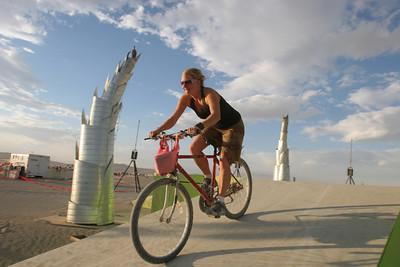 A playa girl on her bike rides through an art instalation