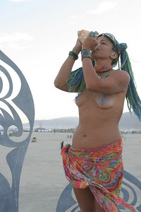Playa Girl Blowing on some type of sea shell instrument
