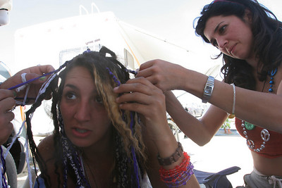 Sandra on the right helps brade a woman´s hair.