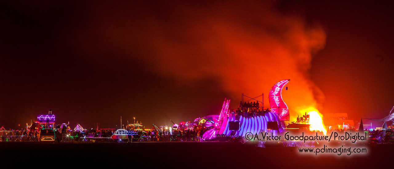 An art piece on the playa is burned, surrounded by burners, bicycles and art cars.