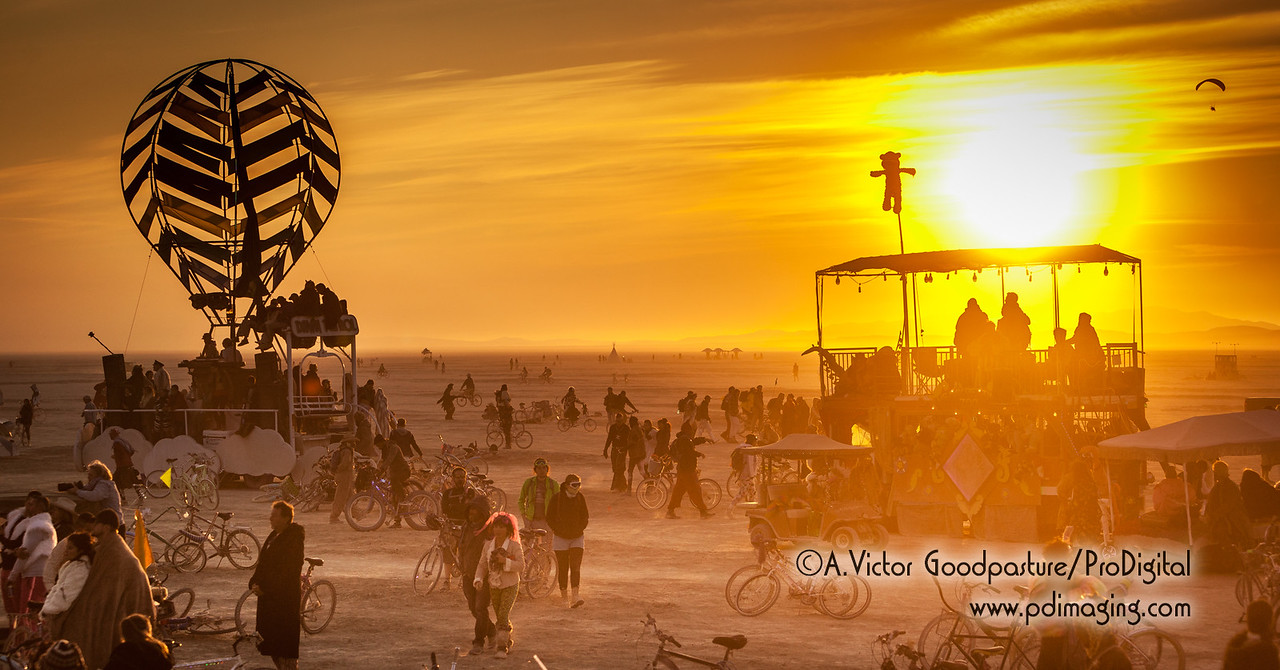 Burners on foor, bike and art car watch the burn. A skydiver makes a morning jump.