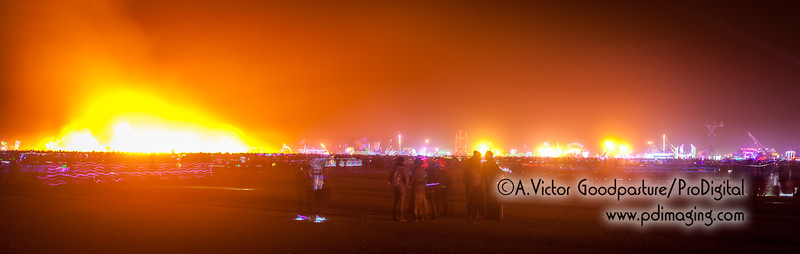 The crowd is now moving toward the fiery pile after fire officals deem it safe. In the background is the mass of art cars that surround the entire burn.