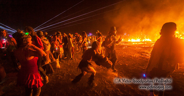 With the fire still burning, burners approach in costume and various stages of undress to celebrate and party.