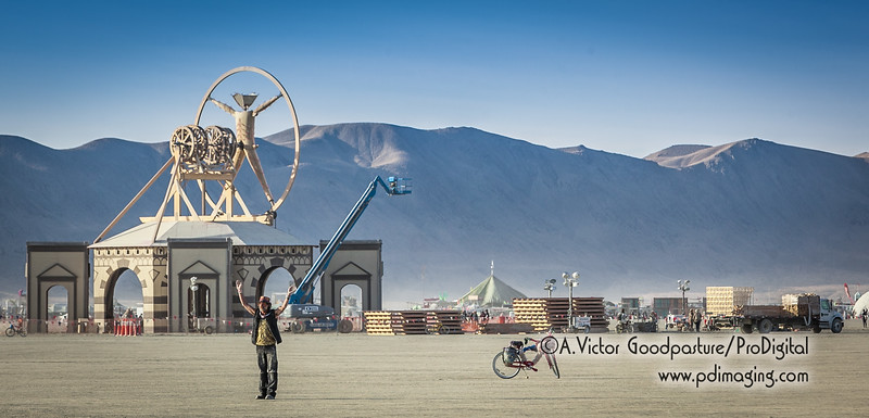 A burner meditates on the playa while workers prep The Man for the evening's burning.