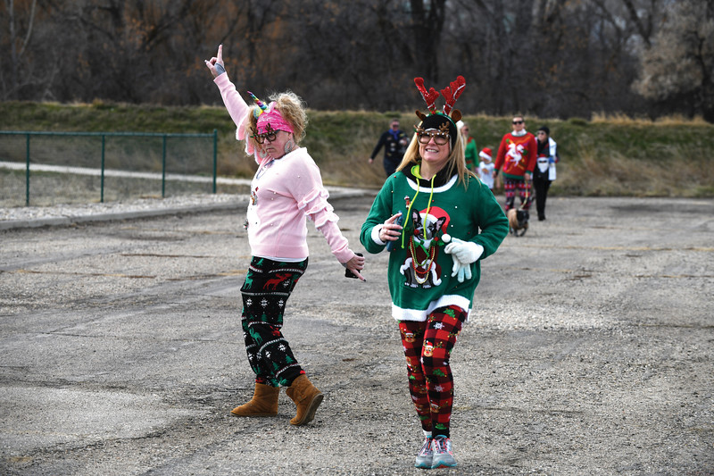 Matthew Gaston | The Sheridan Press<br>Festive unicorn Amy Bosh left celebrates triumphantly while Jennifer Dahmer right takes a more reserved approach to finishing the CHAPS Ugly Sweater 5K Saturday, Dec. 1, 2018.