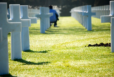 An ROTC Army Cadet pauses by a gravestone at the Normandy American Cemetery