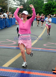 5/8/2010 Mike Orazzi | Staff Mary Csontos raises her arms as she crosses the finish line during the women's 5K run at the Connecticut Race In The Park at Walnut HIll Park in New Britain on Saturday morning.