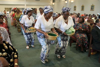 Members of the Catholic Women Association of Cameroon lead the offertory procession down the center aisle of Mary Our Queen Church.