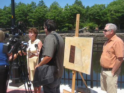 Media interviewing Mayor Pluta, while artist Dean Nimmer (right) stands by one of his paintings.