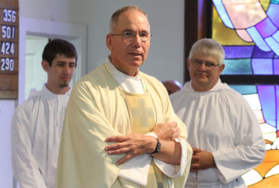 As the last daily Mass at the Cantonment Chapel comes to an end, Father Fred Wendel gives some closing remarks before the final blessing. Standing behind him are altar servers Joey Buchieri, left, and his father Mike, a retired Army lieutenant colonel whose family has worshipped at the chapel since 1990.  (Page 11, June 23, 2011 issue)